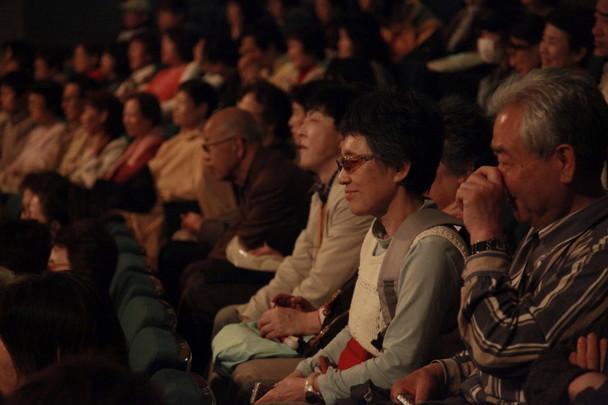 映画を観ながら微笑んでいる視覚障害者のお客さま
