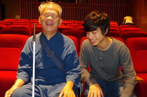 笑顔を浮かべる視覚障害者のおじいちゃんと学生ボランティア